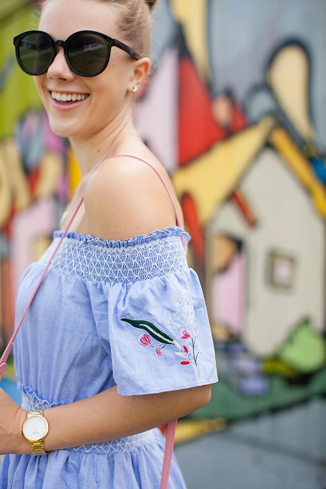 Blogger Bella Bucchiotti of xoxoBella is wearing a Dezzal dress and a Mansur Gavriel bag at the Handshake and Love mural in Houston.
