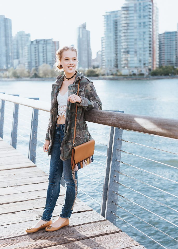 Blogger Bella Bucchiotti of xoxoBella is wearing a Free People camo jacket, embroidered Driftwood jeans, Tory Burch shoes and a Rebecca Minkoff tassel bag in Vancouver.