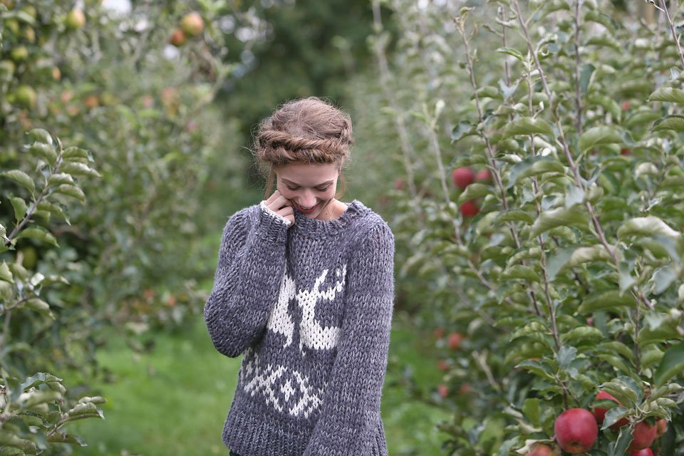 Blogger Bella Bucchiotti of xoxoBella is wearing a Free People sweater and skirt with a fishtail crown braid at an apple orchard.