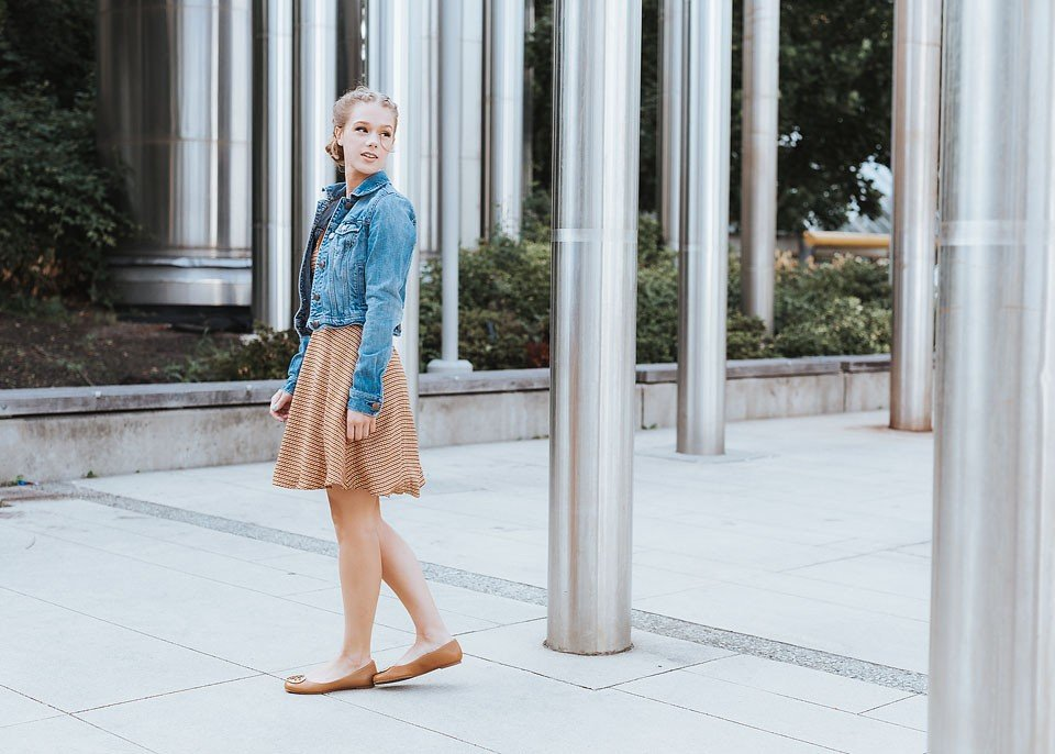 Blogger Bella Bucchiotti of xoxoBella is wearing a Forever 21 dress with a denim jacket, Tory Burch flats and a Rebecca Minkoff bag in Vancouver, BC.