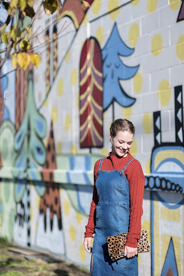 Blogger Bella Bucchiotti of xoxoBella is wearing a Guess sweater and denim dress with a Clare V clutch at a mural in Vancouver, BC.