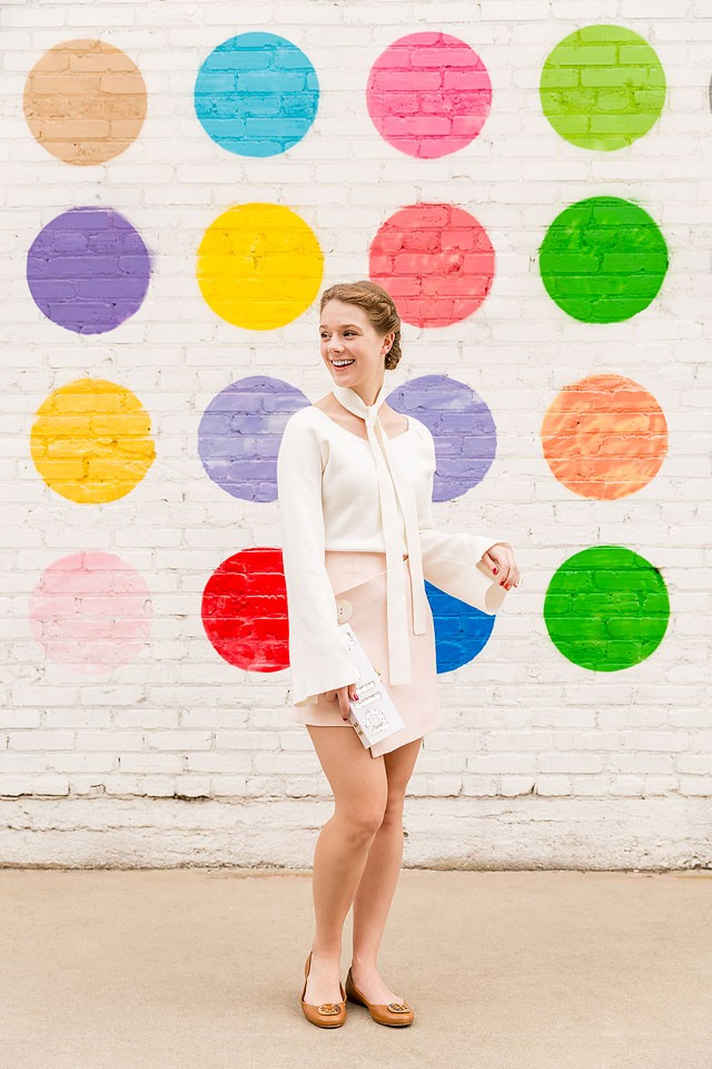 Blogger Bella Bucchiotti of xoxoBella is wearing a Chicwish sweater and skirt with Tory Burch flats at a polka dot mural in LA.