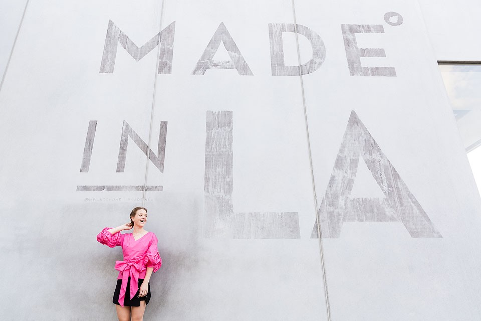 Blogger Bella Bucchiotti of xoxoBella is wearing a Chicwish blouse and skirt with velvet sneakers at the Made in LA mural.