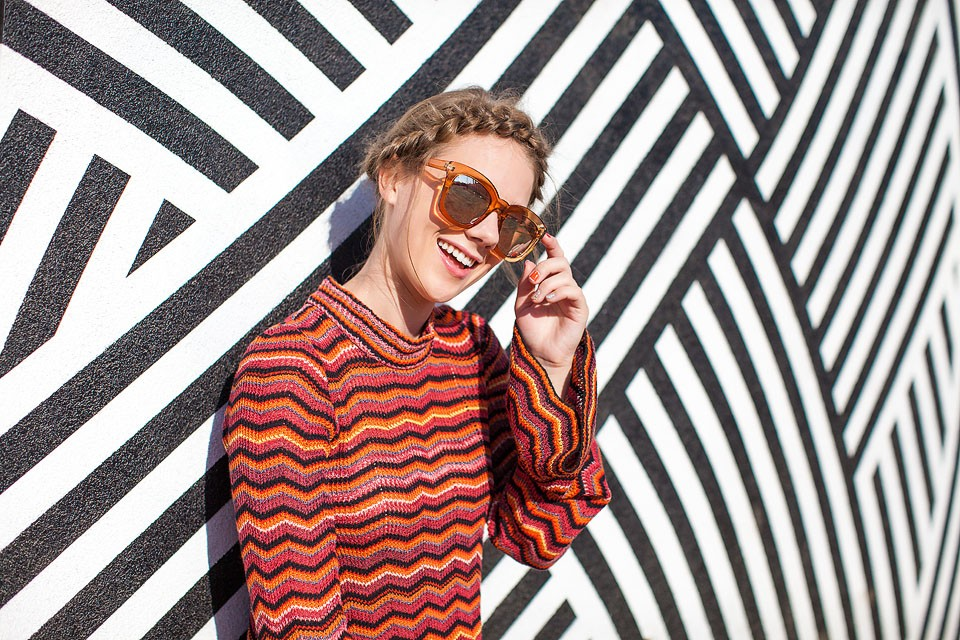 Blogger Bella Bucchiotti of xoxoBella is wearing a Free People mini dress and Sam Edelman velvet sneakers at a mural in Venice, California.