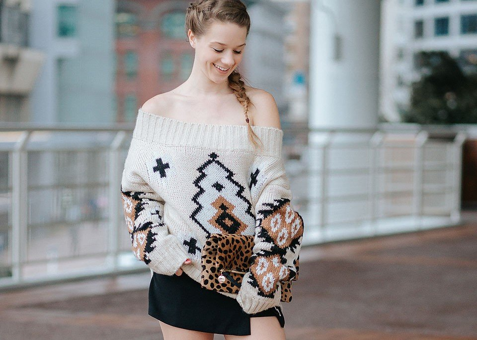 Blogger Bella Bucchiotti of xoxoBella is wearing a chunky sweater from Chicwish and a lace up skirt from Chicwish. She also has a Clare V clutch.