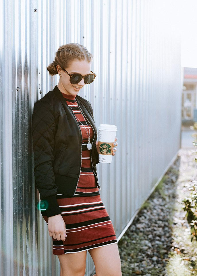 Blogger Bella Bucchiotti of xoxoBella is wearing a ribbed jersey dress and bomber from H&M and Steve Madden wedge sneakers.