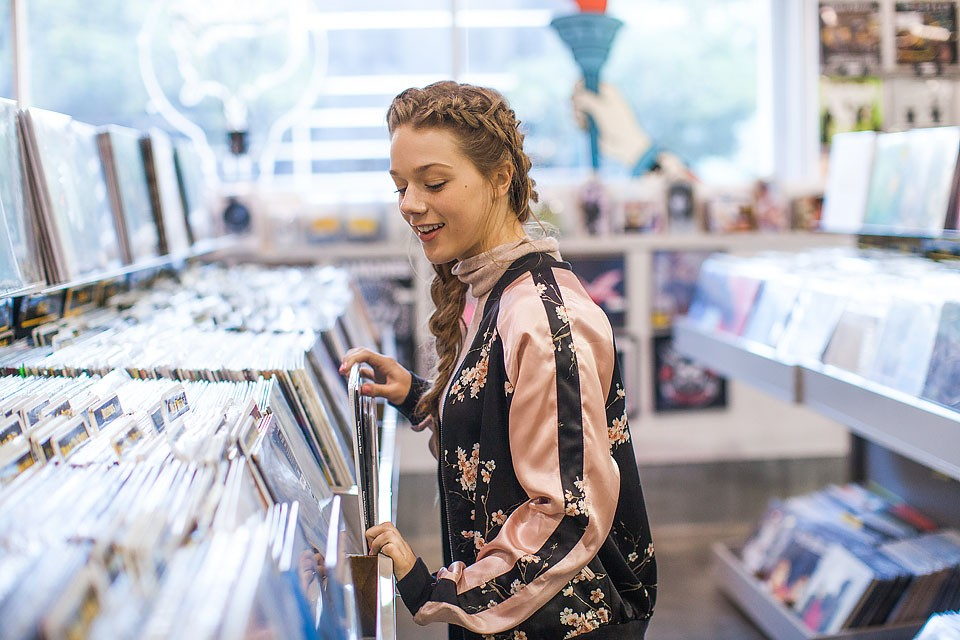 Blogger Bella Bucchiotti of xoxoBella is wearing a sweater dress and floral bomber jacket at Amoeba Records in LA.