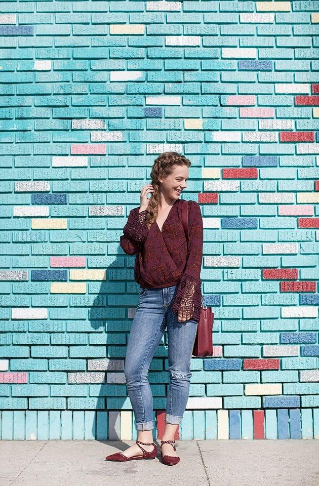 Blogger Bella Bucchiotti of xoxoBella is wearing a Sun & Shadows burgundy bell sleeve top, Driftwood jeans, Halogen flats and a Rebecca Minkoff bag at a mural in Santa Monica, California.