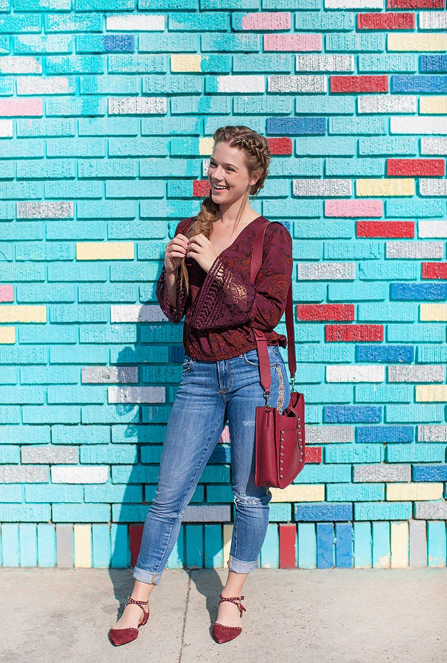 Blogger Bella Bucchiotti of xoxoBella is wearing a Sun & Shadows burgundy bell sleeve top, Driftwood jeans, Halogen flats and a Rebecca Minkoff bag at a mural in Santa Monica, California.