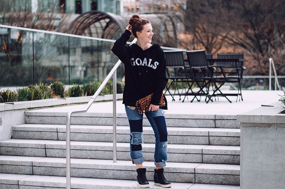 """Blogger Bella Bucchiotti of xoxoBella is wearing a Free People """"Goals"""" hoodie, Noisy May patchwork jeans and wedge sneakers."""