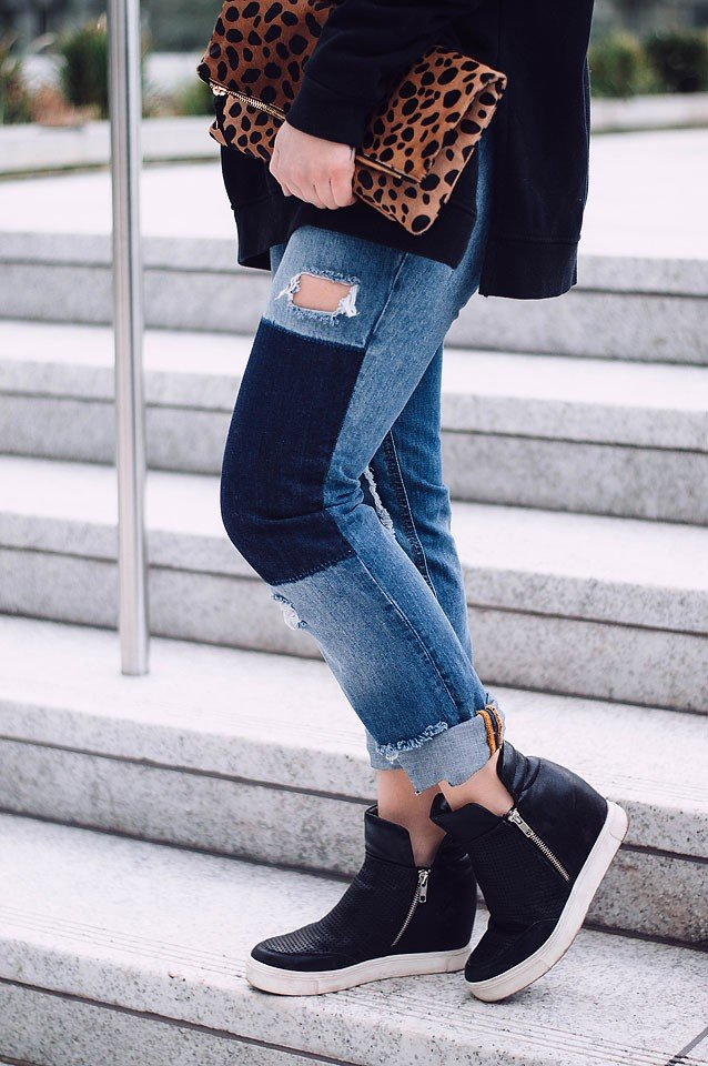 "Blogger Bella Bucchiotti of xoxoBella is wearing a Free People ""Goals"" hoodie, Noisy May patchwork jeans and wedge sneakers."