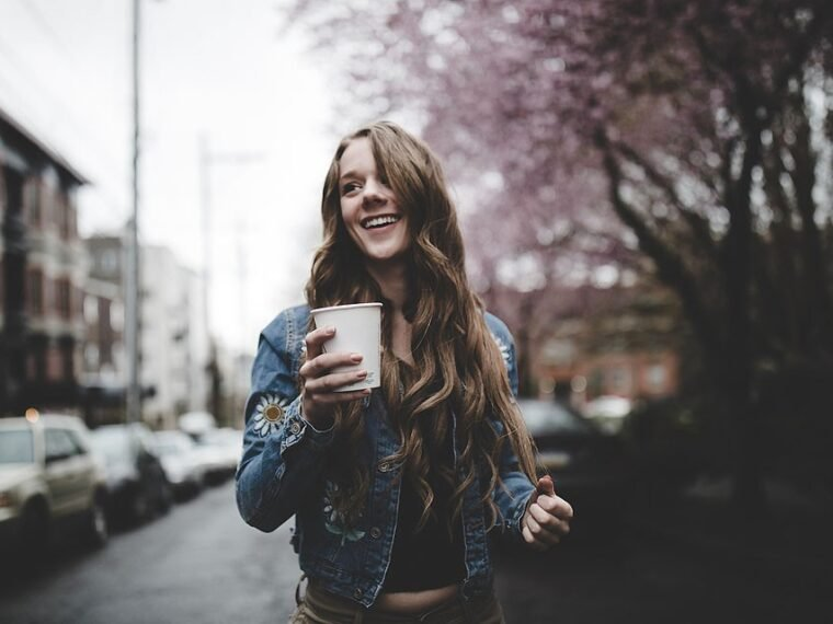 Blogger Bella Bucchiotti of xoxoBella.com shares a pair of Levis jeans and a Forever 21 embroidered denim jacket. Photo taken in Seattle with blossoms.