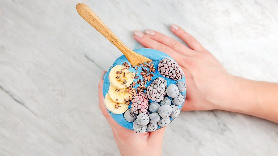 Blogger Bella Bucchiotti of xoxoBella.com shares a recipe for a fruity blue smoothie bowl that is made with blue spirulina.