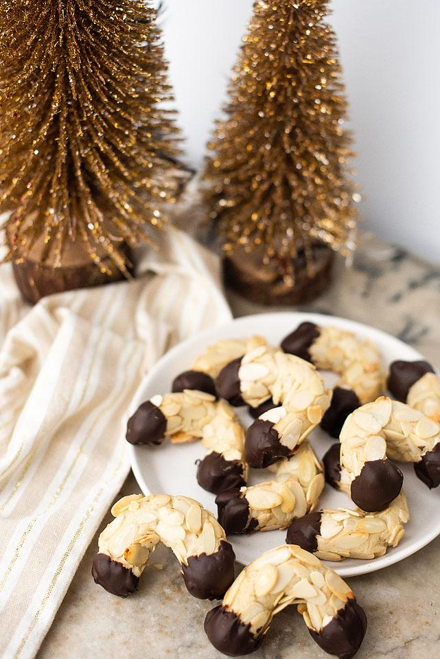 Food blogger, Bella Bucchiotti of xoxoBella shares a holiday baking recipe for chocolate dipped almond horns. You will love these Christmas cookies and they are a great addition to your Christmas baking.