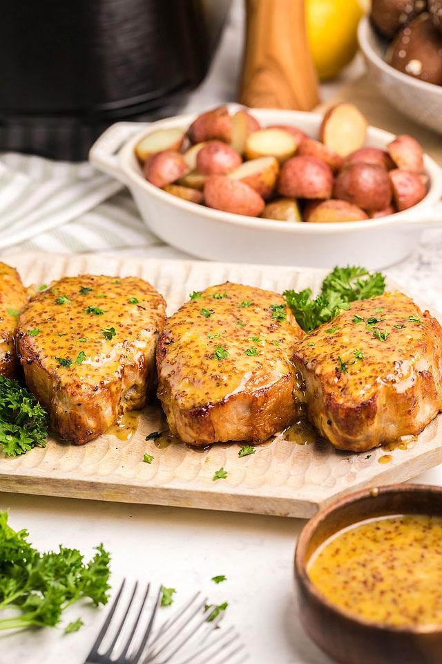 Food blogger, Bella Bucchiotti of xoxoBella shares a recipe for air fryer honey mustard pork chops. You will love this 30 minute meal.
