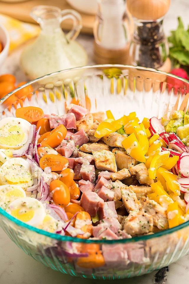 Food blogger, Bella Bucchiotti of xoxoBella, shares a recipe for Cobb salad with garlic cilantro dairy free ranch dressing. You will love this filling dinner salad!