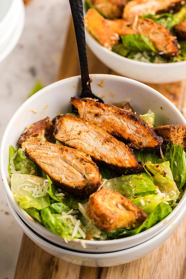 Food blogger, Bella Bucchiotti of xoxoBella, shares a recipe for blackened chicken Caesar salad with air air fryer homemade croutons and the best homemade Caesar dressing.