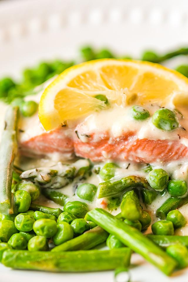 Food blogger, Bella Bucchiotti at xoxoBella, shares salmon and fresh vegetables with a creamy white wine sauce. You will love this easy salmon recipe and cream sauce for salmon, too.