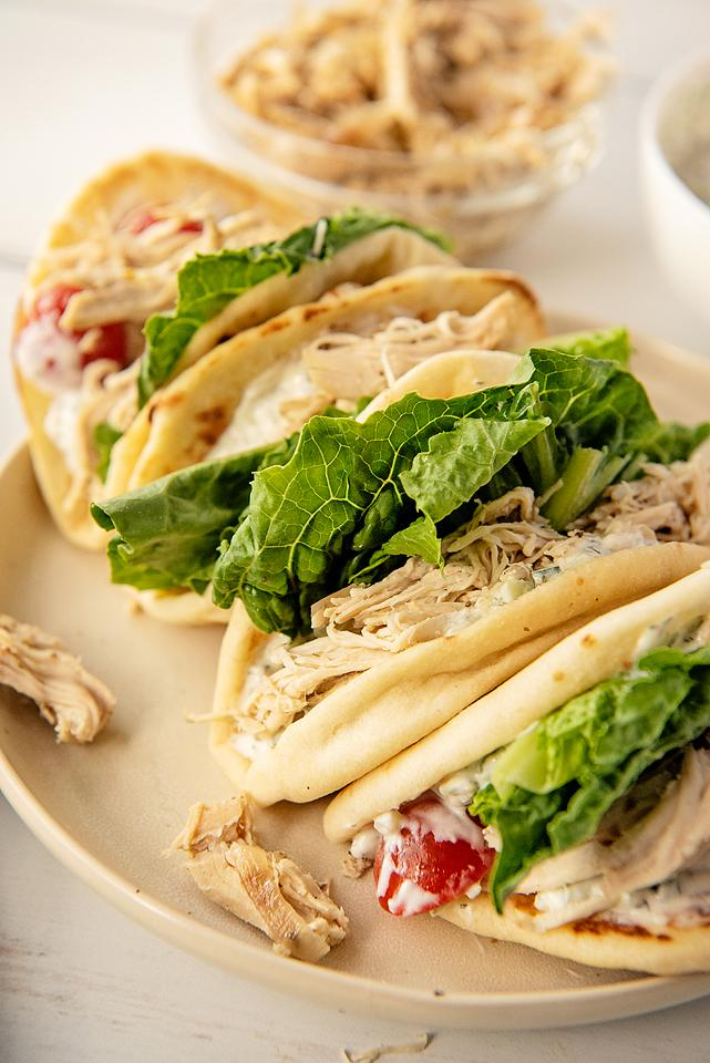Food blogger, Bella Bucchiotti of xoxoBella, shares a recipe for slow cooker Greek shredded chicken gyros with homemade tzatziki sauce. You will love this easy crock pot chicken recipe!