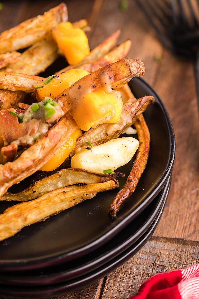Food blogger, Bella Bucchiotti of xoxoBella, shares a Canadian poutine recipe with meat. You will love these smothered fries with cheese curds, bacon and gravy.