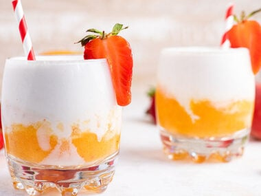 Food blogger, Bella Bucchiotti of xoxoBella shares a layered coconut mango tropical rum slushie recipe. You will love this frozen mango cocktail!