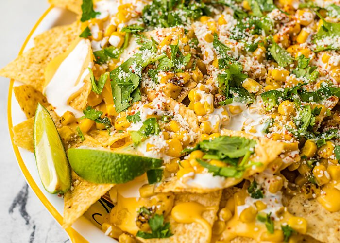 Food blogger, Bella Bucchiotti of xoxoBella, shares elote Mexican street corn nachos with zesty cheese sauce. You will love these unique nacho toppings!