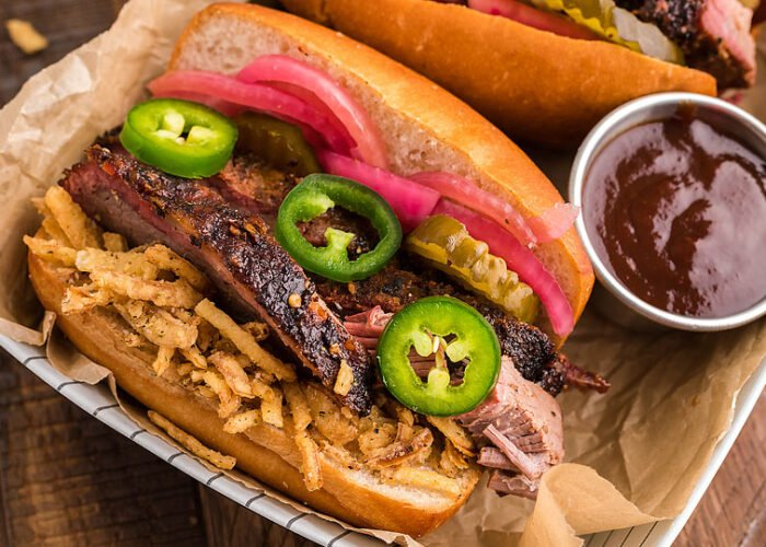 Food blogger, Bella Bucchiotti of xoxoBella, shares a smoked brisket sandwich with homemade pickled red onions. It is the best BBQ brisket sandwich!