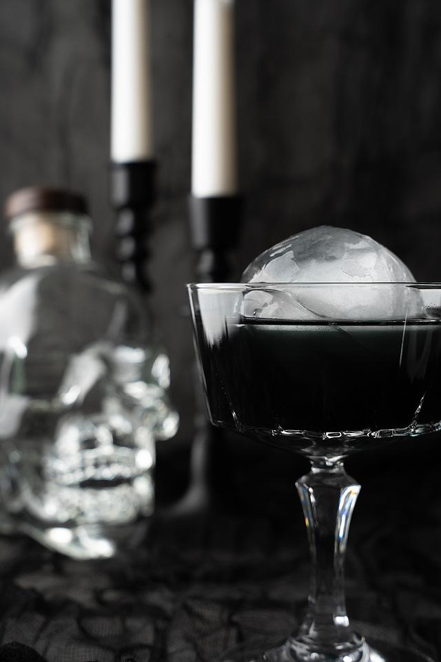 Food blogger, Bella Bucchiotti of xoxoBella, shares a black Halloween cosmopolitan cocktail. You will love this cocktail with an ice ball.