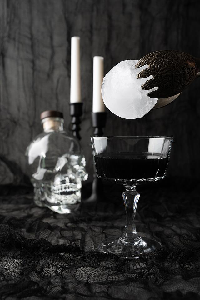 Food blogger, Bella Bucchiotti of xoxoBella, shares a black Halloween cosmopolitan cocktail. You will love this Halloween vodka drink.
